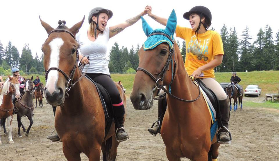 Liz Smith and Thalia Ochoa riding on rescue horses Sid and Kesler